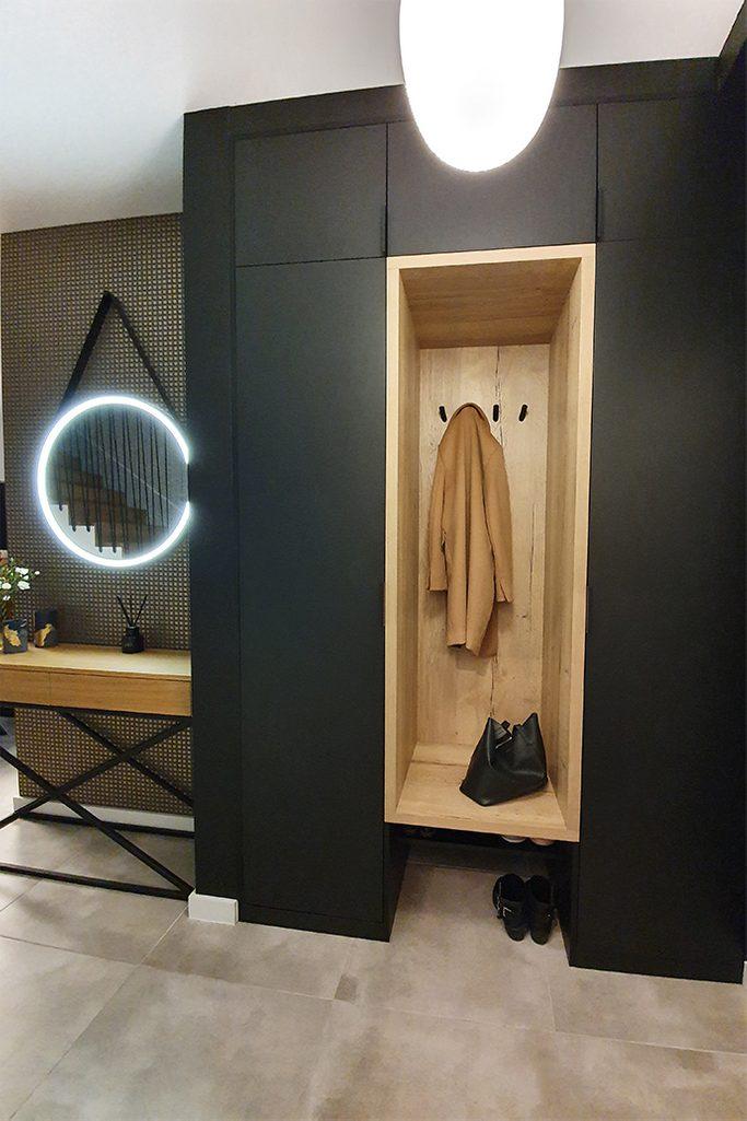 czarne ściany w przedpokoju, wnęka na wieszaki, lustro z oświetleniem, loftowy stolik do przedpokoju