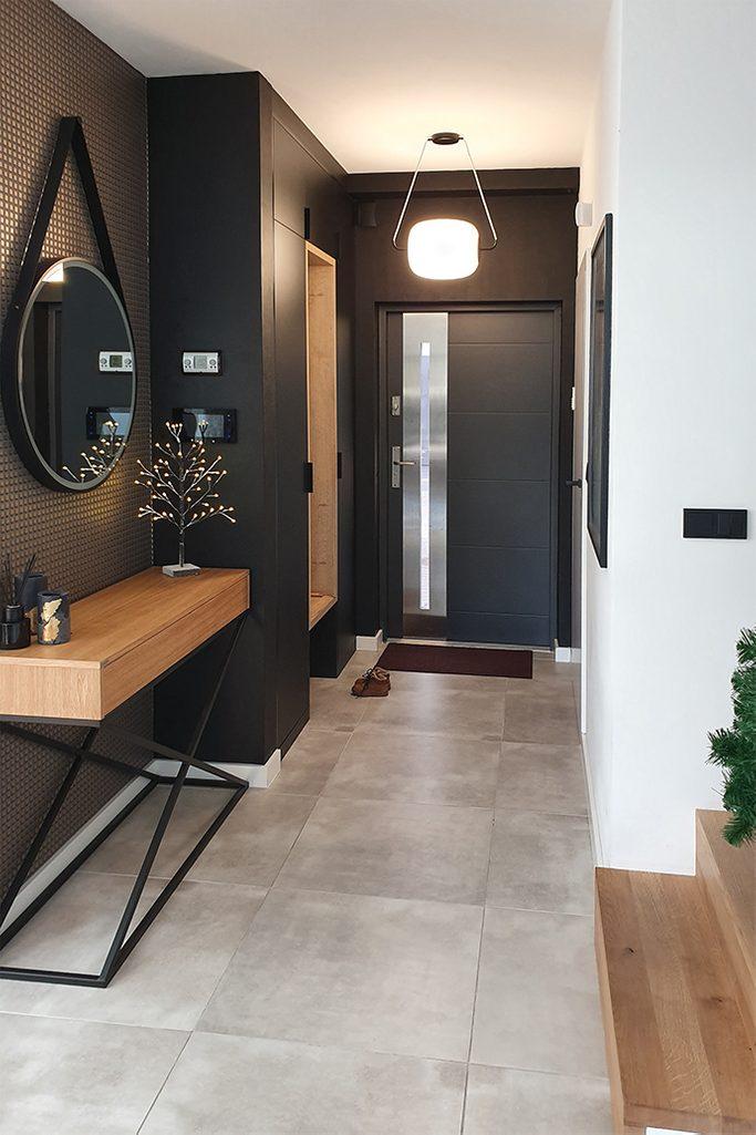 czarno-biały przedpokój, loftowy stolik w przedpokoju, drewno i metal, czarne ściany w holu