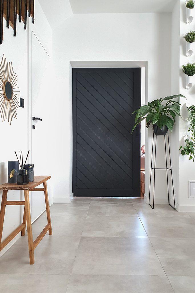 drzwi przesuwne w przedpokoju, czerń i biel w aranżacji wnętrza, kwiaty w przedpokoju