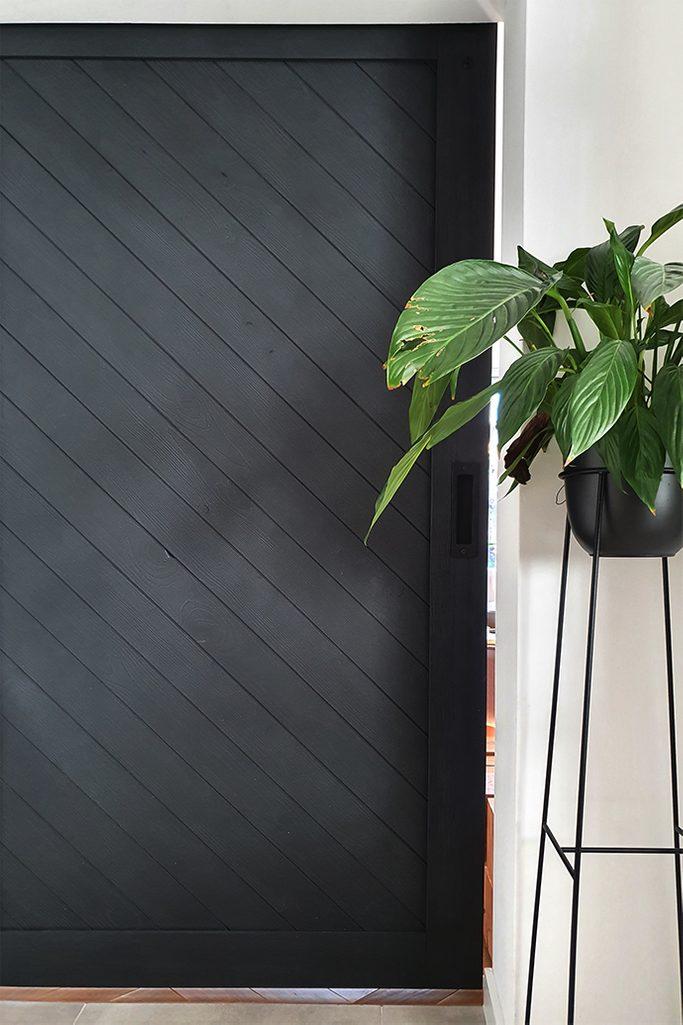czarne drzwi przesuwne, wysoki metalowy stojak na kwiaty