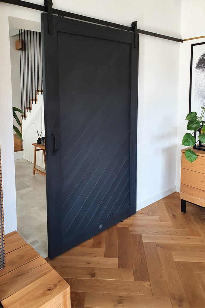 eleganckie drzwi przesuwne w kolorze czarnym, wejście do salonu z drzwiami przesuwnymi