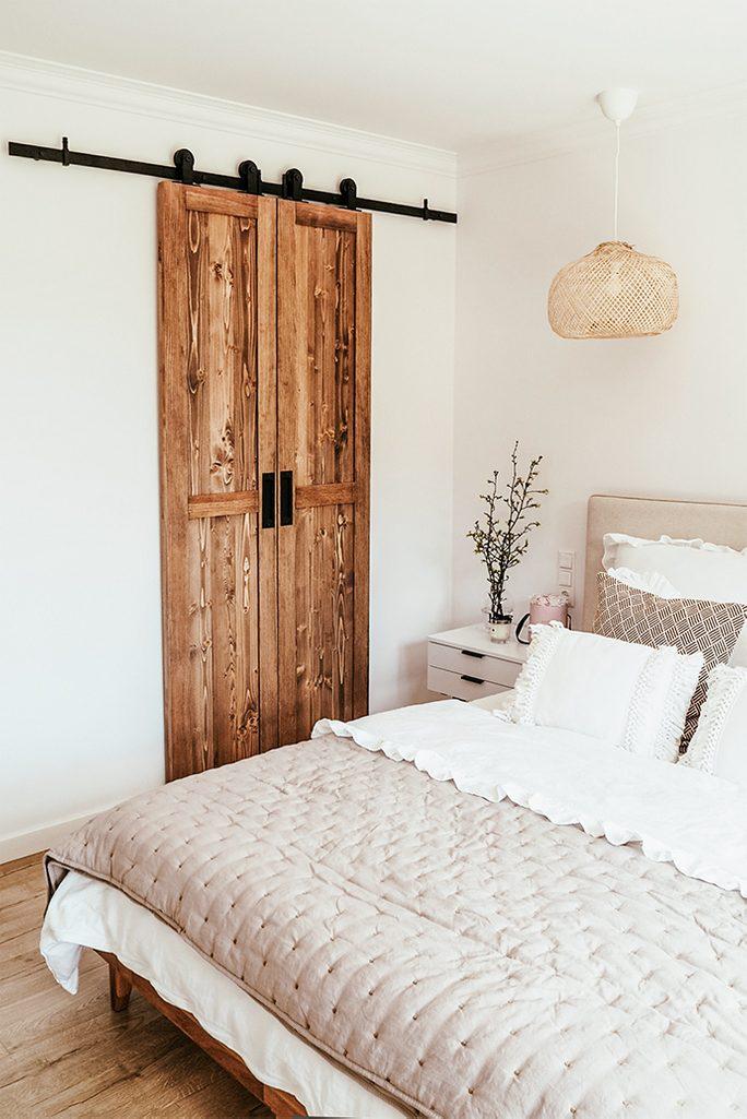 wąskie drzwi przesuwne, drzwi do garderoby, biel i drewno w sypialni, poduszki w stylu boho