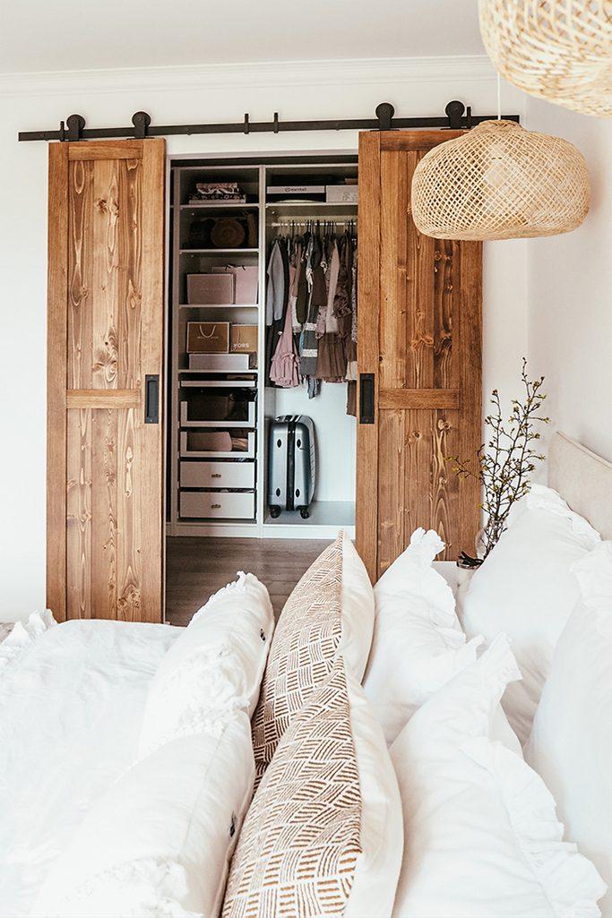garderoba w sypialni, rozsuwane drzwi przesuwne, drewno i biel, ozdobne poduszki na łóżko