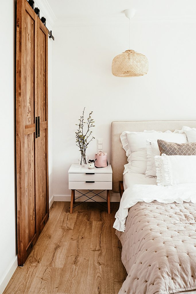 garderoba w sypialni, drzwi przesuwne do garderoby, biel i drewno, naturalny beż, ozdobne poduszki, biały stolik nocny