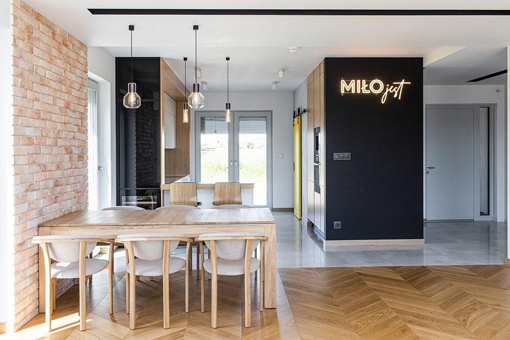 nowoczesna kuchnia, otwarta kuchnia, cegła na ścianie w kuchni, kącik jadalny, duża otwarta kuchnia, dekoracje neonowy napis, żółte drzwi do spiżarni, przesuwne drzwi do spiżarni