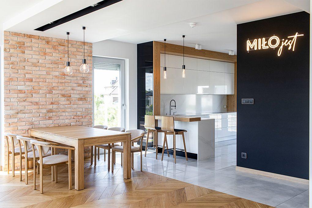 kącik jadalny w kuchni, duża otwarta kuchnia, industrialne lampy w kuchni, dekoracja neonowy napis, białe meble w kuchni, meble kuchenne na wysoki połysk