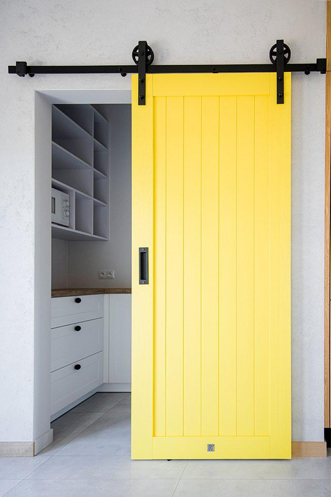 żółte drzwi przesuwne, przesuwne drzwi do schowka, unikalny system przesuwny, żółte drzwi, nowoczesna kuchnia, wejście do spiżarni, żółte drzwi drewniane