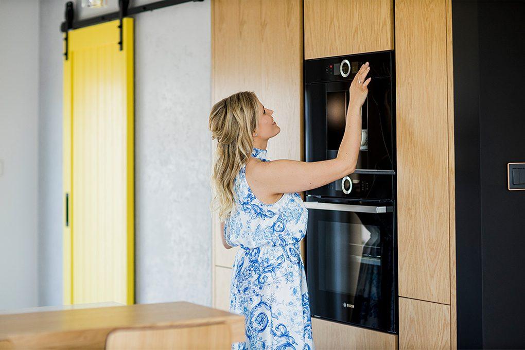 nowoczesna kuchnia, żółte drzwi przesuwne, drzwi przesuwne w kuchni, duża kuchnia, zabudowa kuchenna, elementy drewniane w kuchni. kuchnia ze spiżarnią