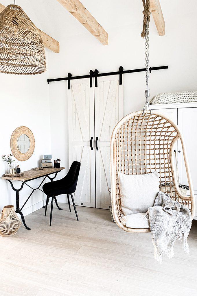 wiszący fotel w sypialni, drewniane belki w sypialni, rustykalny styl, drzwi do garderoby, biel i drewno, rustykalna biel, mała toaletka, toaletka z czarnymi nogami, ażurowa lampa w sypialni, jasno i przytulnie