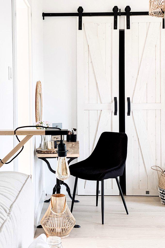 sypialnia z garderobą, sypialnia w stylu rustykalnym, wąskie drzwi przesuwne, drzwi przesuwne do garderoby, białe drzwi, rustykalna biel, czarne dekoracje w sypialni