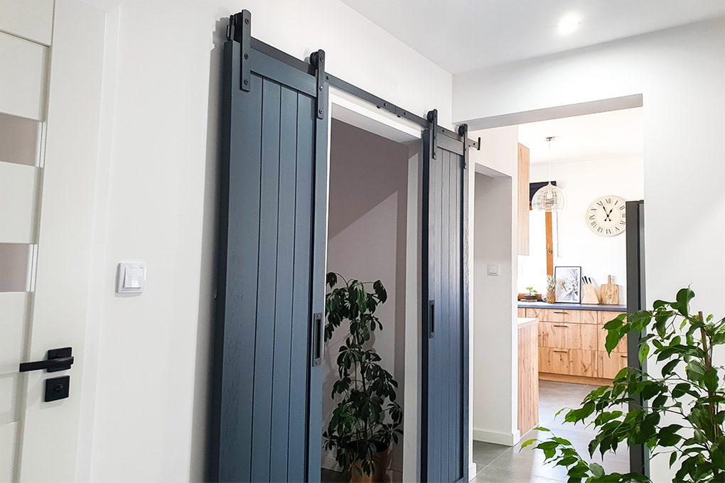 antracytowe drzwi drewniane, drzwi przesuwne w kolorze antracyt, czarny system przesuwny, drewniane drzwi podwójne, wąskie drzwi przesuwne, okucia do drzwi przesuwnych, drzwi do przedsionka, drewniana zabudowa w kucni, duże kwiaty w przedpokoju