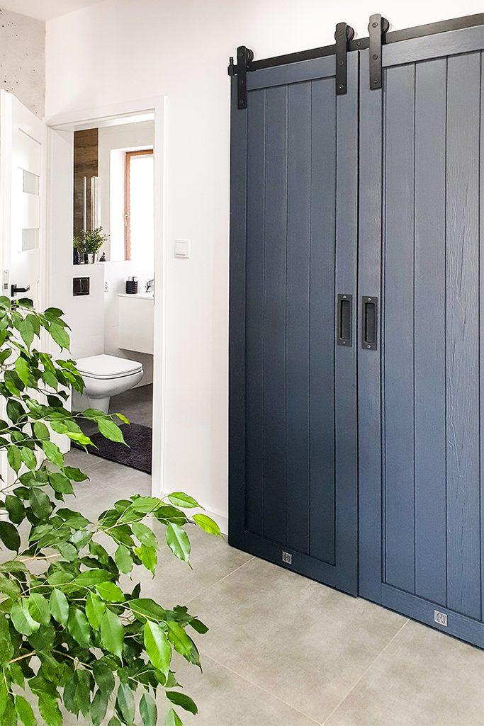 antracytowe drzwi drewniane, wąskie drzwi przesuwne, drzwi przesuwne drewniane, system do drzwi przesuwnych, duże kwiaty w przedpokoju, drewniane drzwi do przedpokoju