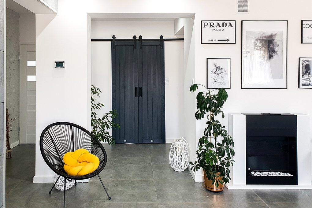 antracytowe drzwi drewniane, antracytowe drzwi, podwójne drzwi przesuwne, drzwi przesuwne w przedpokoju, czarne dodatki we wnętrzu, dodatki w kolorze antracyt, fotografie w czarnej ramie, biel i czerń w nowoczensym domu, nowoczesne wnętrze, komiek w salonie, okrągły fotel ażurowy