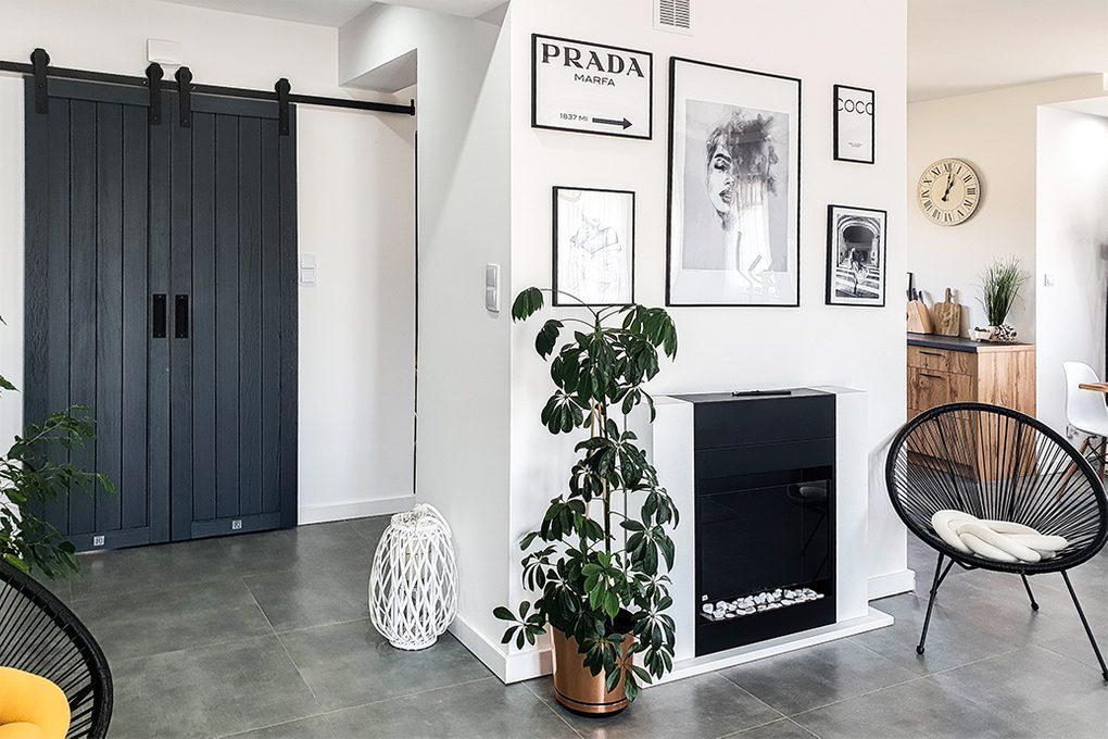antracytowe drzwi drewniane, podwójne drzwi przesuwne, drzwi do przedpokoju, drewniane drzwi w przedsionku, galeria fotografii w czarnych ramkach, ogrągły fotel ażurowy, kominek w salonie, duże kwiaty do salonu, białe ściany czarne dodatki