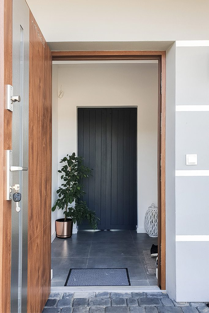 antracytowe drzwi drewniane w przedsionku, rozsuwane drzwi drewniane, drzwi wewnętrzne w kolorze antracytu, antracytowe drzwi w przedsionku, duże kwiaty w przedsionku