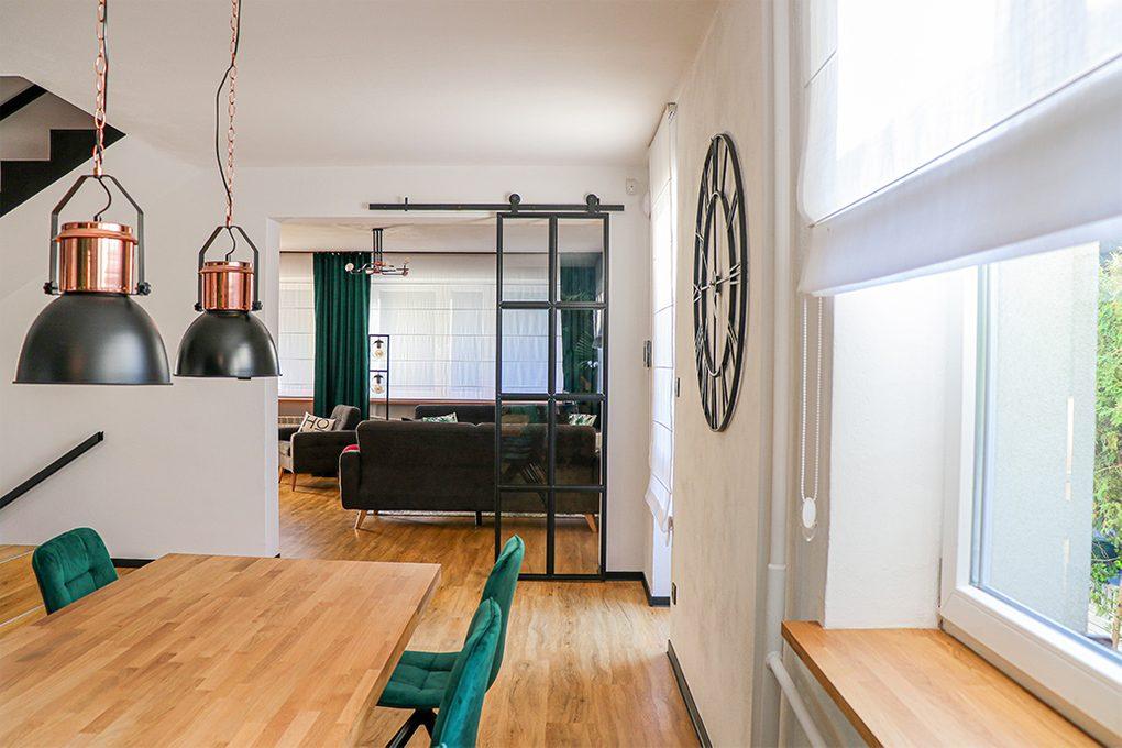 czarny metalowy zegar na ścianę, zegar w stylu industrialnym, loftowe dekoracje, metalowe drzwi ze szkłem, loftowe drzwi, drzwi przesuwne metal szkło, drzwi szkło w czarnej ramie, zielone krzesła do jadalni, salon otwarty na jadalnię, industrialne lampy wiszące w jadalni, duży stół drewniany do jadalni
