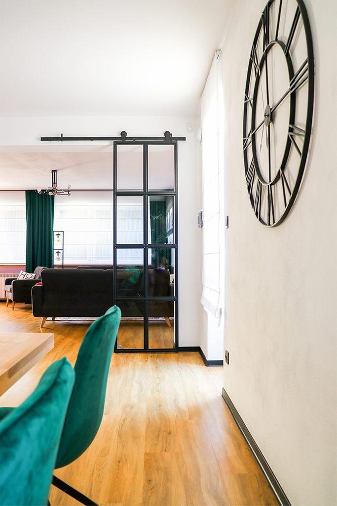 czarny metalowy zegar na ścianę, zegar w stylu industrialnym, loftowe dekoracje, metalowe drzwi ze szkłem, loftowe drzwi, drzwi przesuwne metal szkło, drzwi szkło w czarnej ramie, zielone krzesła do jadalni, salon otwarty na jadalnię, zielone zasłony