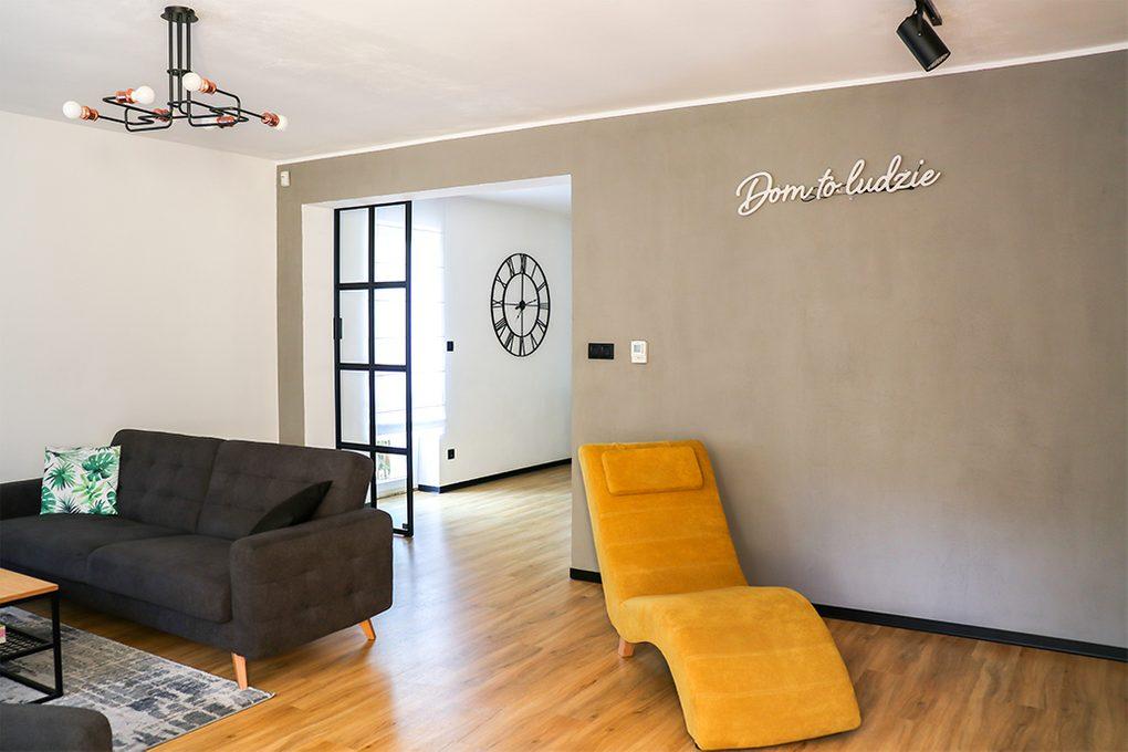 otwarty salon, szara sofa w salonie, industrialna lampa w salonie, żółty fotel do salonu, szara ściana w salonie, salon otwarty na jadalnię, metalowe drzwi ze szkłem, drzwi przesuwne ze szkłem, drzwi w stylu loft, neonowy napis na ścianę, neonowe dekoracje