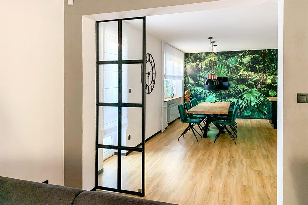 salon otwarty na jadalnię, otwarty salon, drzwi przesuwne ze szkła i metalu, metalowe drzwi przesuwne ze szkłem, drzwi loftowe, industrialne lampy wiszące do jadalni, tapeta botaniczna, dekoracyjna tapeta, duży stół drewniany, zielone krzesła do jadalni