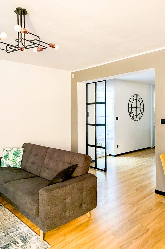 loftowe wnętrze, szklane drzwi w metalowej ramie, szklane drzwi przesuwne, industrialna lampa w salonie, szara sofa, otwarty salon, industrialny zegar na ścianę