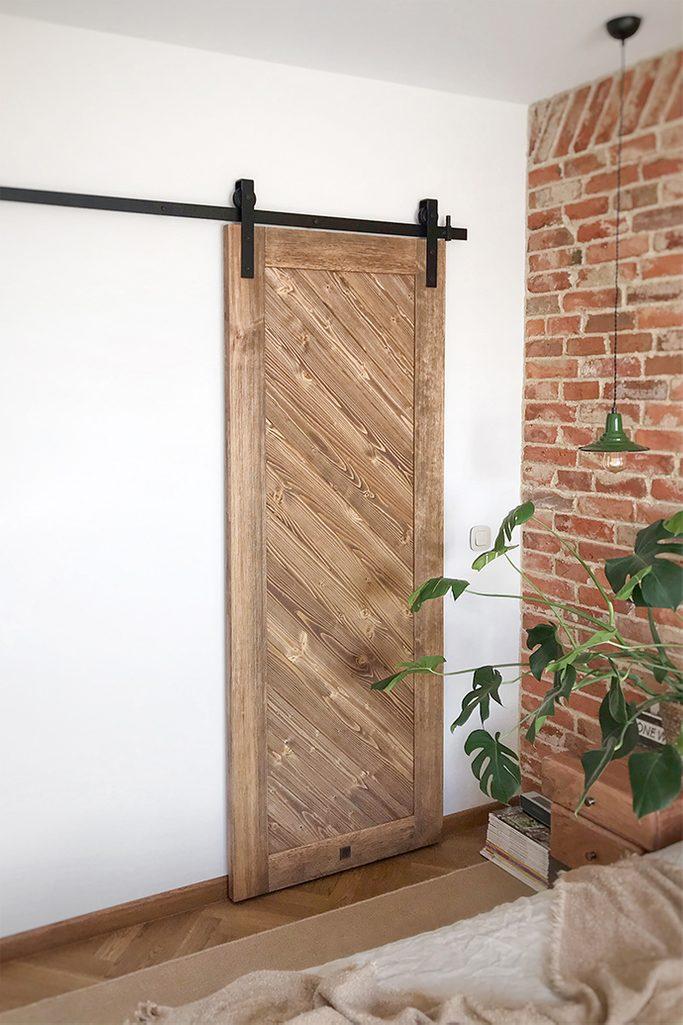 drewniane drzwi przesuwne, drzwi do garderoby, garderoba w sypialni, przesuwne drzwi do garderoby, drewniane drzw, cegła w sypialni, lampka nocna wisząca, styl vintage, vintage sypialnia