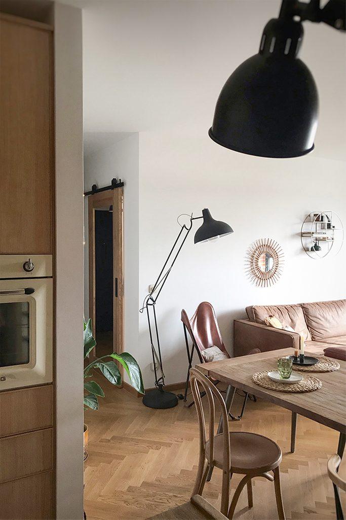 drzwi przesuwne do gabinetu, drewniane drzwi z lustrem, drzwi przesuwne z lustrem, duża lampa metalowa stojąca, skórzany fotel na metalowej podstawie, fotel vintage, parkiet w salonie, lustro w korytarzu, krzesła retro