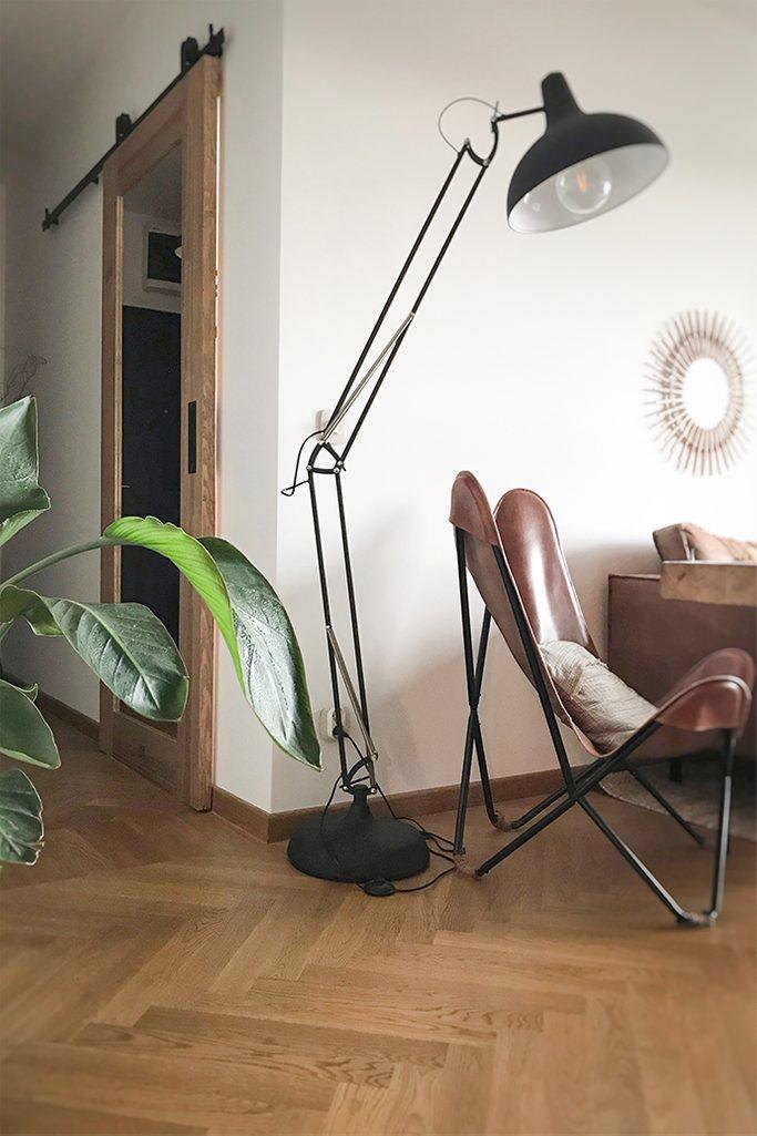 drzwi przesuwne do gabinetu, drewniane drzwi z lustrem, drzwi przesuwne z lustrem, duża lampa metalowa stojąca, skórzany fotel na metalowej podstawie, fotel vintage, parkiet w salonie, lustro w korytarzu