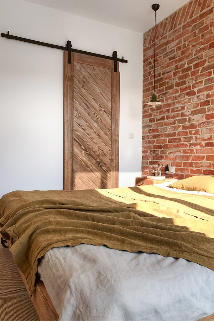 drewniane drzwi przesuwne, cegła na ścianie w sypialni, drzwi przesuwne do garderoby, sypialnia z garderobą, sypialnia w sylu loft, metalowa lampka wisząca do sypialni