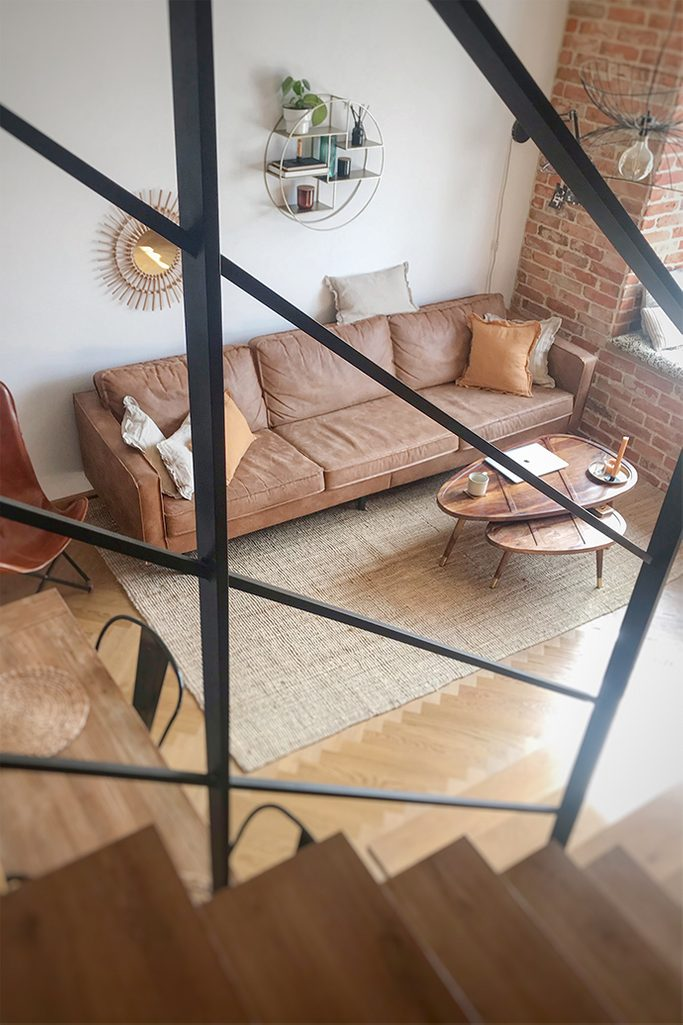 mieszkanie w stylu loft, cegła w mieszkaniu, styl vintage, industrialne elementy dekoracyjne, metalowa półka na ścianę, retro sofa, komplet stolików kawowych, stoliki drewniane
