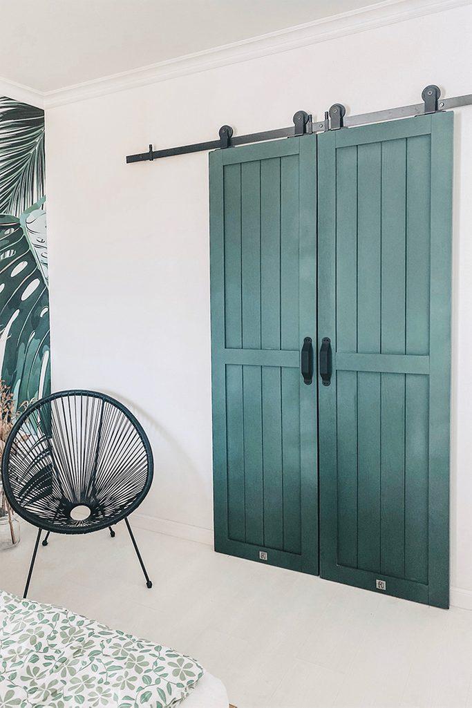 krzesło ażurowe czarne obok podwójnych zielonych drzwi przesuwnych