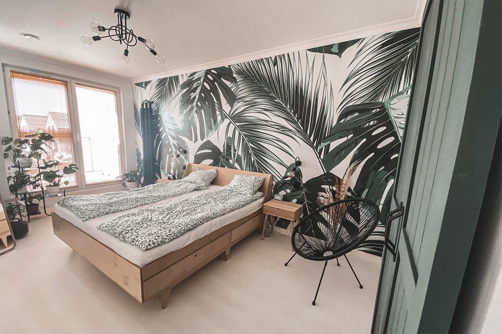 wnętrze sypialni z jasnym drewnianym łóżkiem, dekoracyjną tapetą z motywem roślinnym i czarnym krzesłem ażurowym