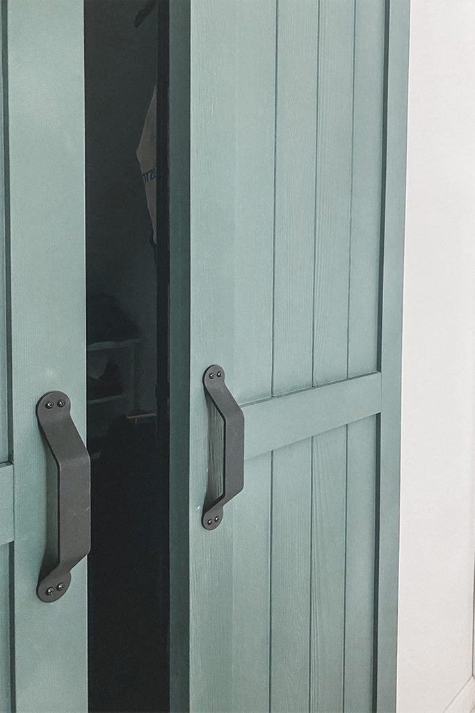 lekko otwarte zielone wąskie drzwi przesuwne odsłaniające garderobę
