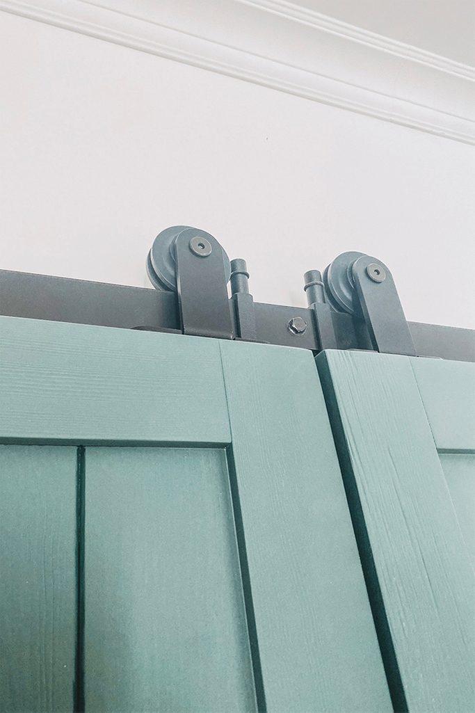 zielone drzwi drewniane z zamontowanym czarnym systemem przesuwnym