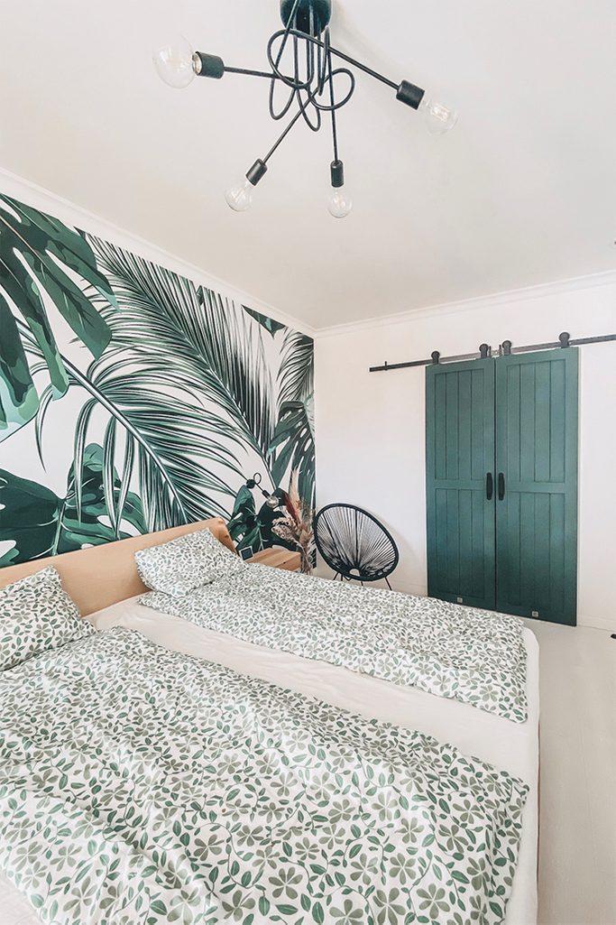 jasna sypialnia z dekoracyjną tapetą roślinną i garderobą ukrytą za zielonymi drzwiami przesuwnymi