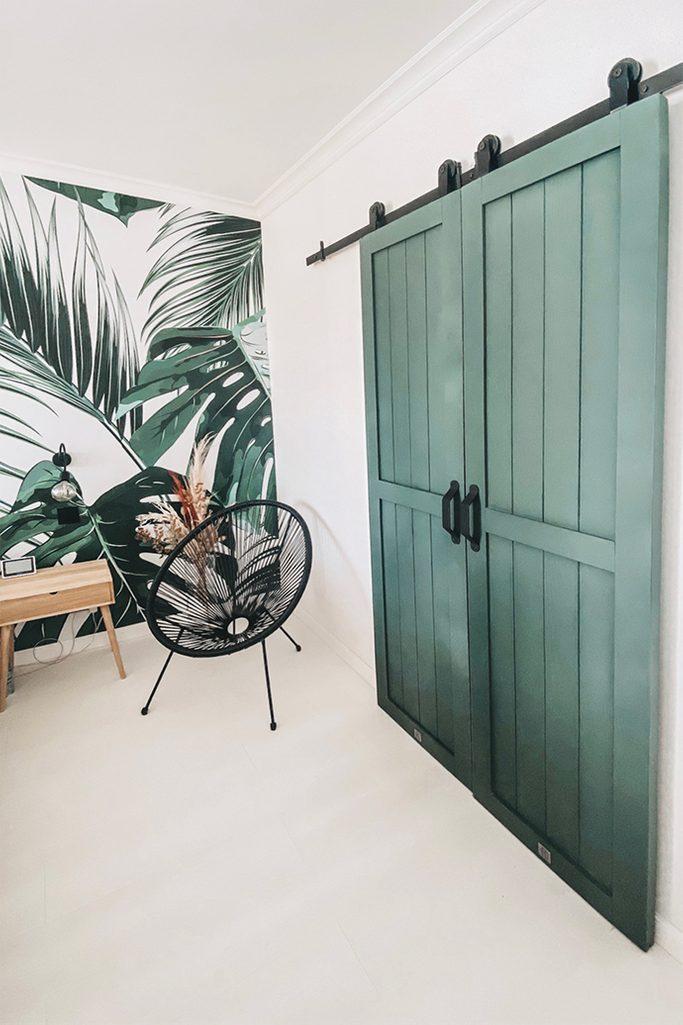 podwójne zielone drzwi przesuwne w sypialni z dekoracyjną tapetą