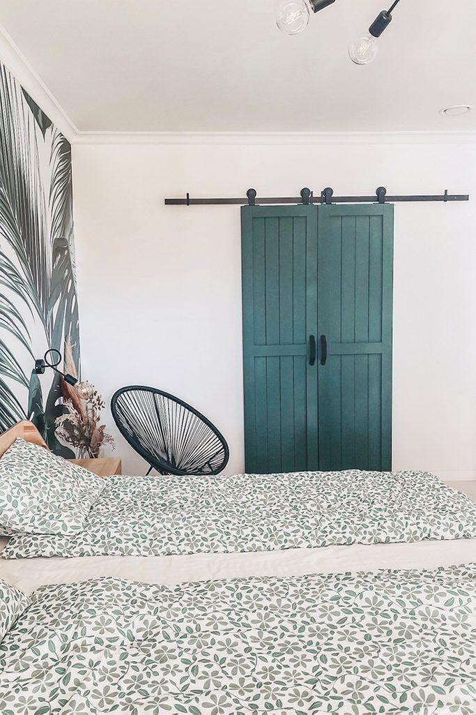 wąskie zielone drzwi przesuwne zamontowane na ścianie w sypialni