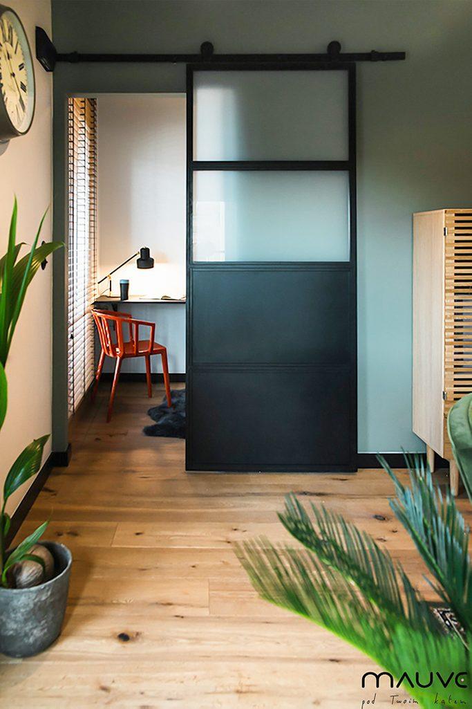 Industrialne drzwi przesuwne wypełnione mlecznym szkłem otwarte na mały kącik pracy z biurkiem