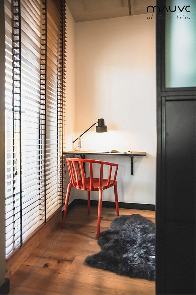 Kącik do pracy z małym biurkiem, metalową lampką i czerwonym krzesłem