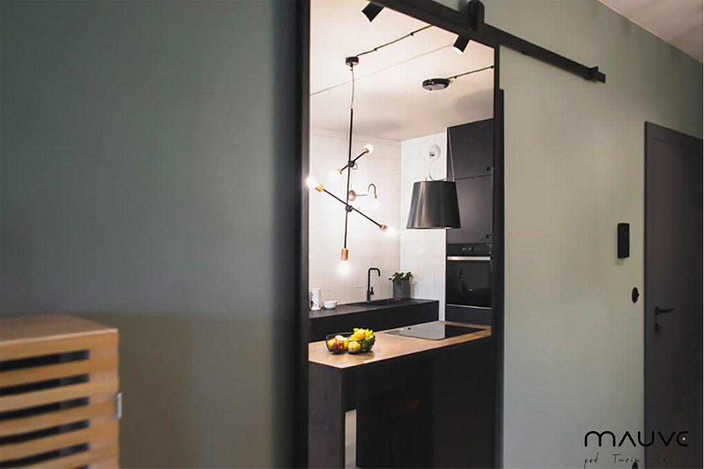 Industrialne drzwi przesuwne z lustrem w małym mieszkaniu