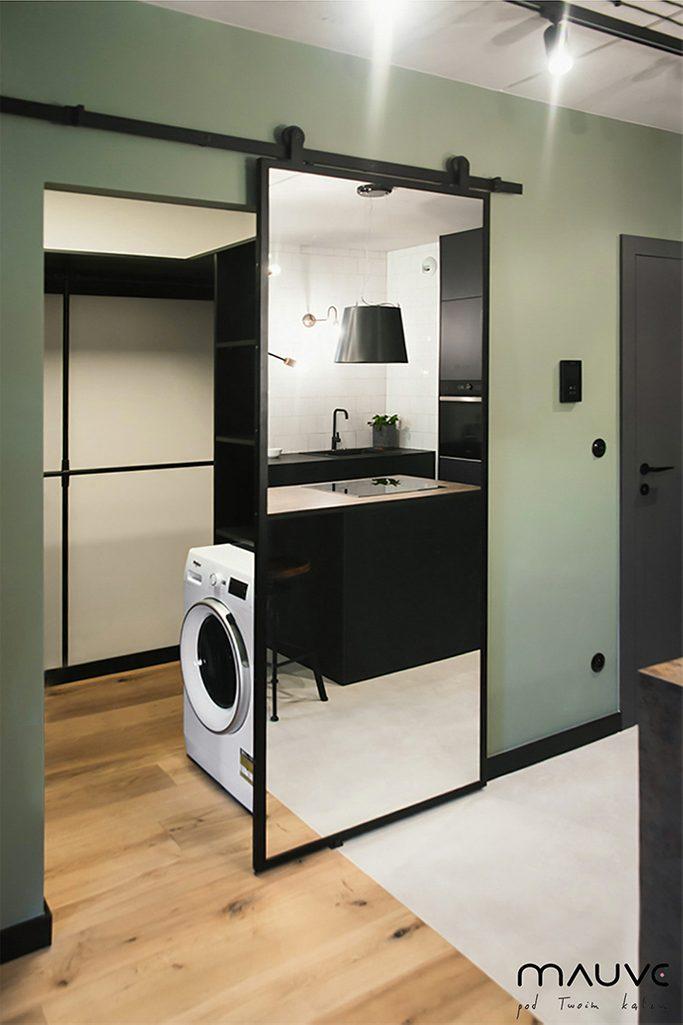 Industrialne drzwi przesuwne z lustrem w wejściu do łazienki w małym mieszkaniu