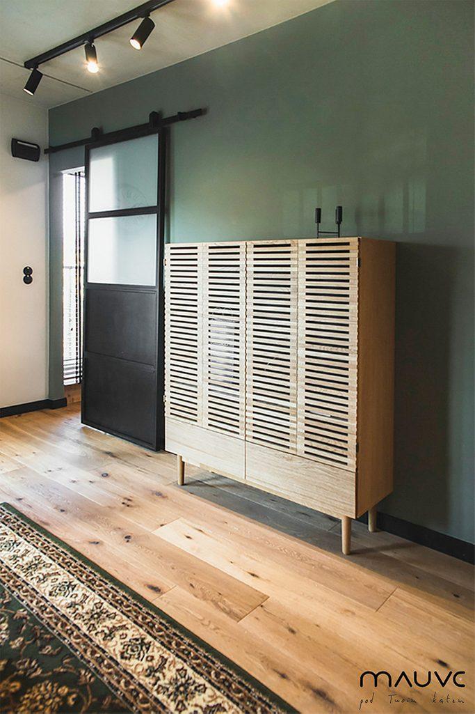 Komoda w stylu vintage obok drzwi przesuwnych z metalu i szkła