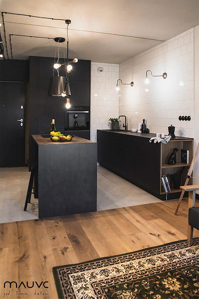 Otwarta kuchnia w kolorach czerni i bieli oświetlona metalowymi lampami w stylu industrialnym
