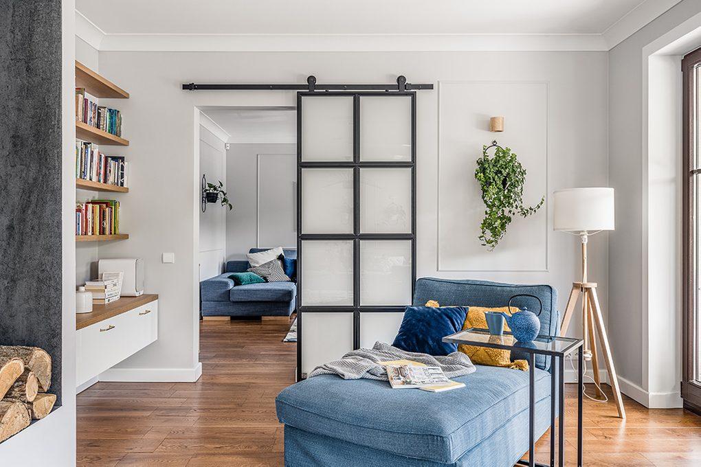 Kącik do czytania z niebieską kanapą oddzielony od salonu drzwiami przesuwnymi ze szkłem mlecznym