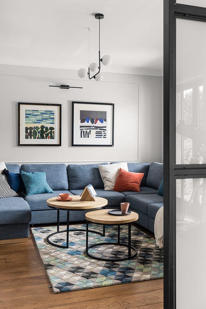 Duża niebieska sofa i komplet okrągłych stolików kawowych w strefie wypoczynkowej