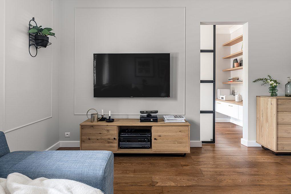 Kącik telewizyjny z szafką RTV z jasnego drewna obok przesuwnych drzwi z metalu i szkła
