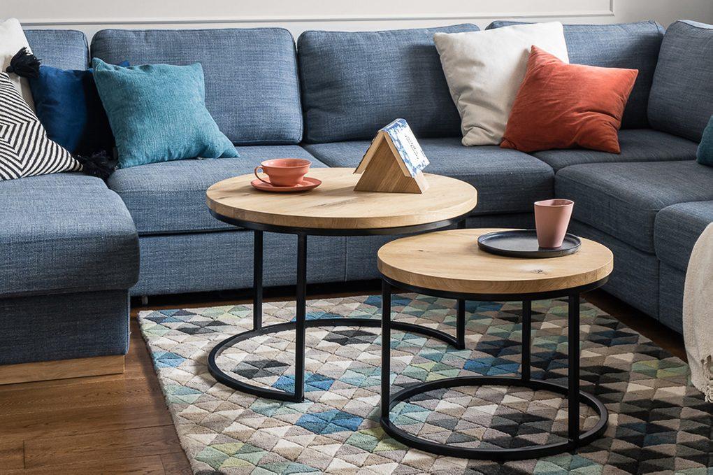 Zestaw dwóch okrągłych stolików kawowych z jasnego drewna i metalu na tle dużej niebieskiej sofy