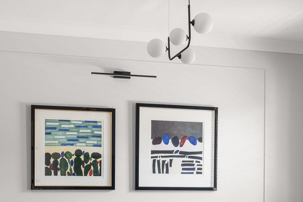Metalowy żyrandol i obrazy w czarnych ramkach na tle jasnej ściany