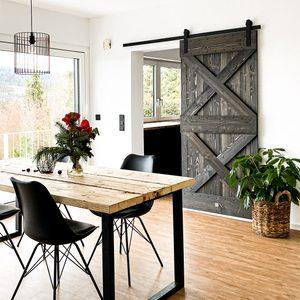 Industrialny stół z drewna i metalu przed drewnianymi drzwiami przesuwnym prowadzącymi do kuchni