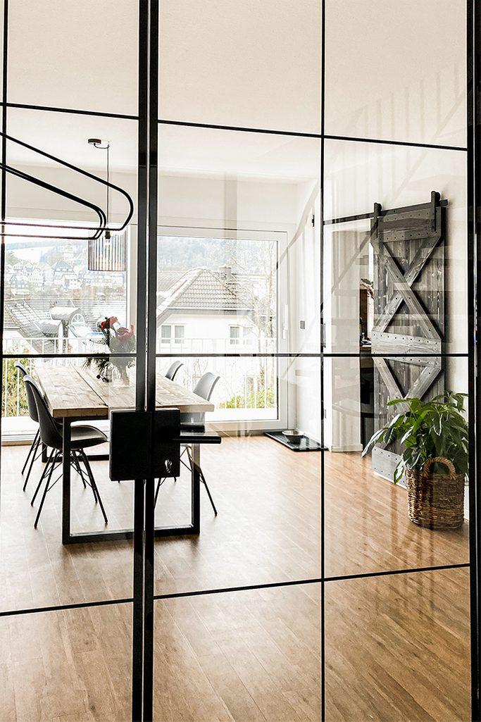 Jasna i przestronna jadalnia za szklanymi drzwiami w metalowej ramie