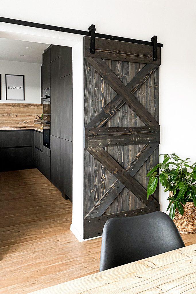 Otwarte drzwi przesuwne z drewna ukazujące fragment kuchni z ciemną zabudową